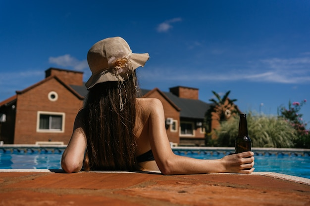 Bela jovem relaxando na piscina