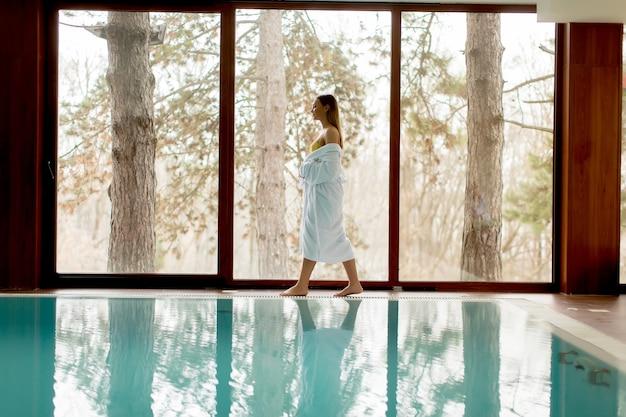 Bela jovem relaxante à beira da piscina no centro de spa