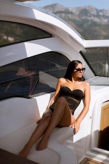 Bela jovem relaxante no iate em dia de sol