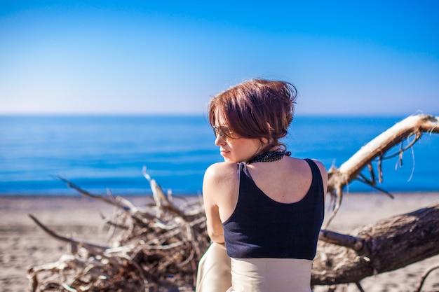 Bela jovem relaxar na praia em dia ensolarado de inverno sozinho