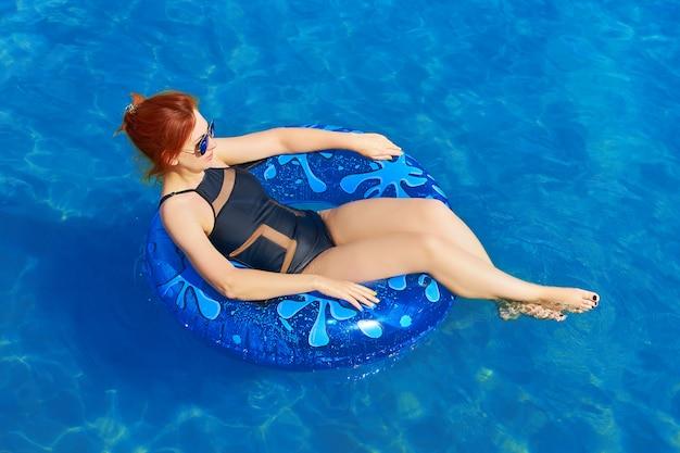 Bela jovem relaxar no anel inflável na água do mar