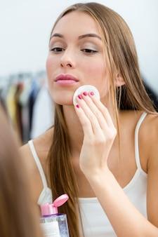 Bela jovem removendo maquiagem perto do espelho em casa.