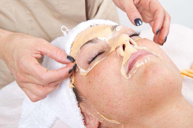 Bela jovem remover máscara facial em um centro de beleza