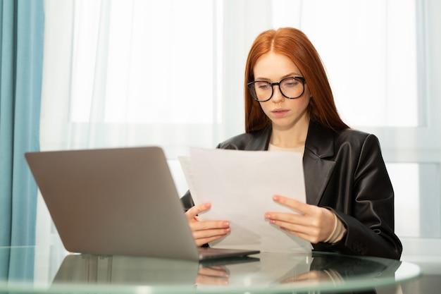 Bela jovem ruiva à mesa com o laptop no escritório