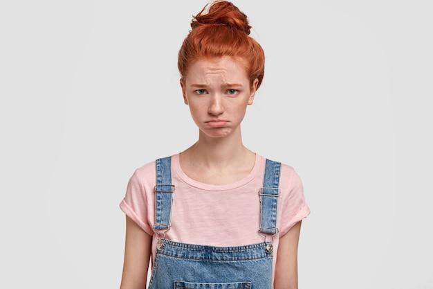 Bela jovem ruiva chateada franze a testa e parece ofendida