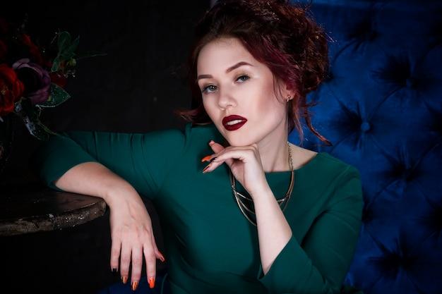 Bela jovem ruiva com maquiagem profissional em vestido verde posando em interior luxuoso no sofá azul