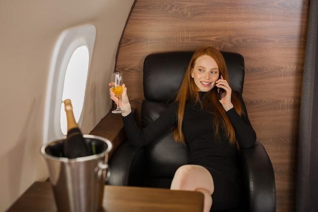 Bela jovem ruiva falando ao telefone na cabine de um jato particular