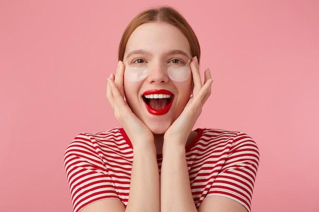 Bela jovem ruiva feliz em uma camiseta listrada vermelha, com lábios vermelhos, toca seu rosto com os dedos, muito satisfeita com as novas manchas. stands.