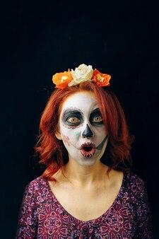 Bela jovem ruiva no dia da fantasia de bruxa arte cara máscara caveira morto em uma parte traseira preta ...