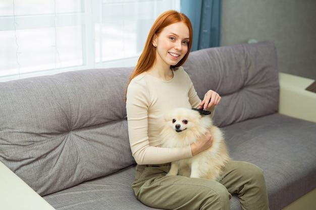 Bela jovem ruiva penteando seu cachorro