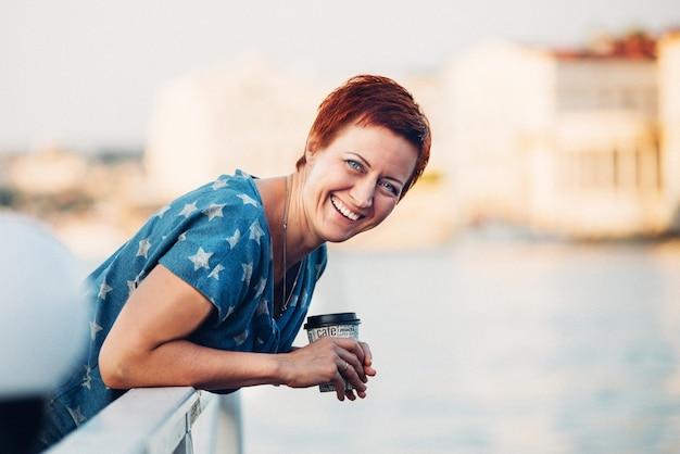 Bela jovem ruiva sorridente com cabelo curto no cais no retrato ao ar livre de blusa e saia jeans.
