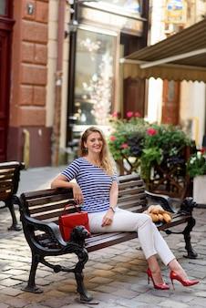 Bela jovem se senta em um banco nas ruas da cidade velha.