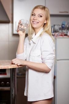 Bela jovem segura um copo com água na cozinha