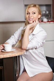 Bela jovem segura uma xícara de café na cozinha
