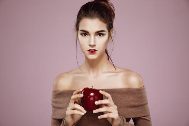 Bela jovem segurando a maçã vermelha nas mãos.