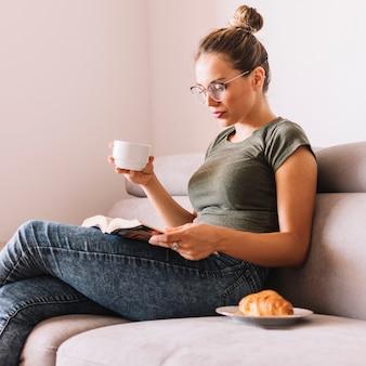 Bela jovem segurando a xícara de café, lendo o livro