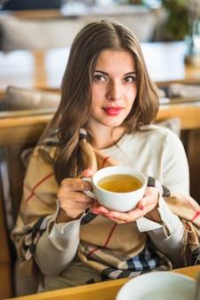 Bela jovem segurando a xícara de chá de ervas
