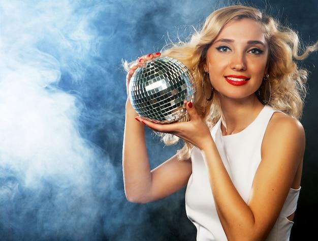 Bela jovem segurando bola de discoteca na boate