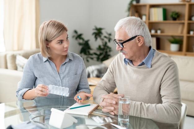 Bela jovem segurando comprimidos enquanto os mostra a seu pai idoso doente e o consulta sobre medicina