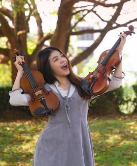 Bela jovem segurando dois violinos nas mãos, com um sentimento de felicidade