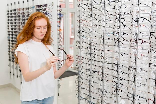 Bela jovem segurando e olhando para o espetáculo na loja de óptica