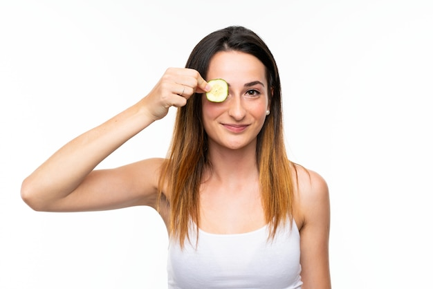 Bela jovem segurando fatias de pepino sobre parede branca isolada