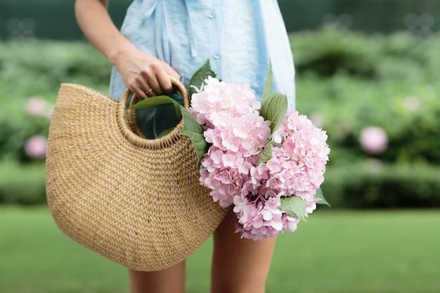 Bela jovem segurando o saco de vime de mão com flores lilás