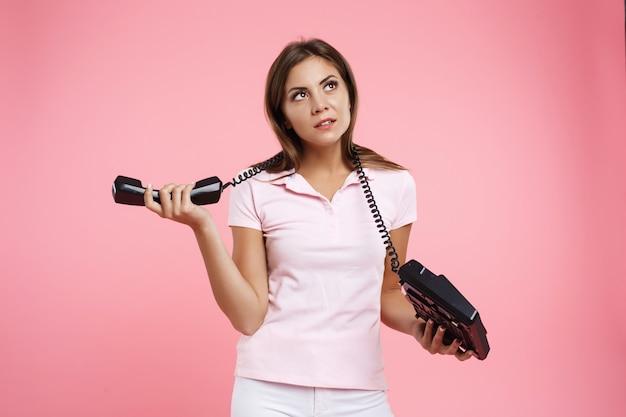 Bela jovem segurando o telefone fixo com fio de telefone em volta do pescoço