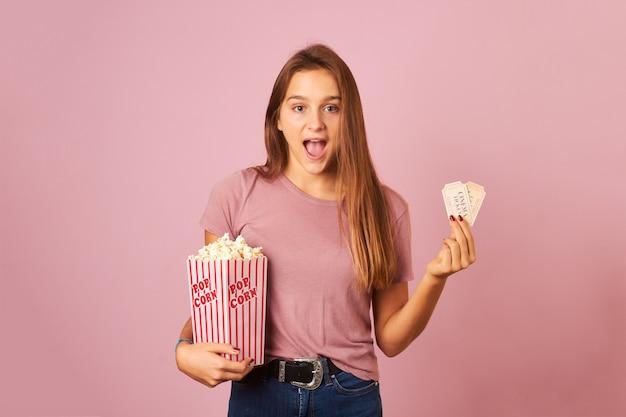 Bela jovem segurando pipoca e ingressos de cinema