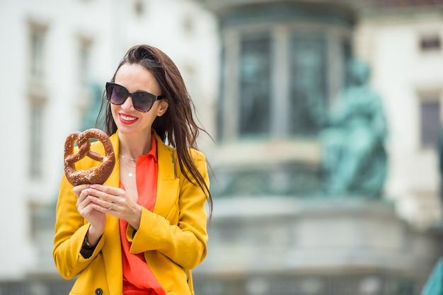 Bela jovem segurando pretzel e relaxar no parque