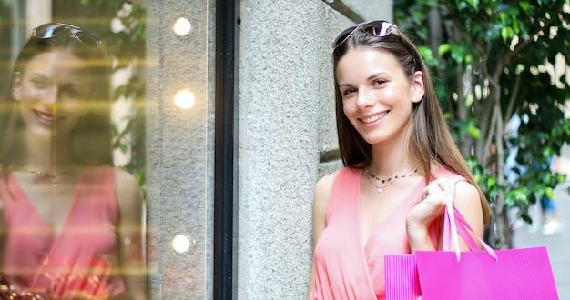Bela jovem segurando sacolas de compras e caminhar ao ar livre em um centro da cidade