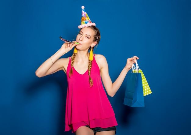 Bela jovem segurando sacolas de compras e comemorando