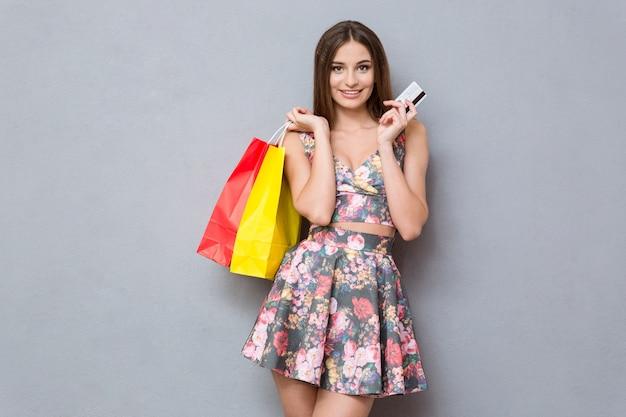 Bela jovem segurando sacolas de compras e um cartão de crédito