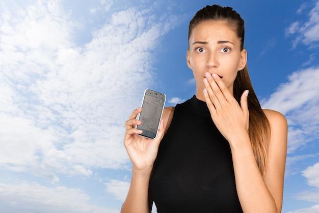 Bela jovem segurando seu celular touch screen quebrado
