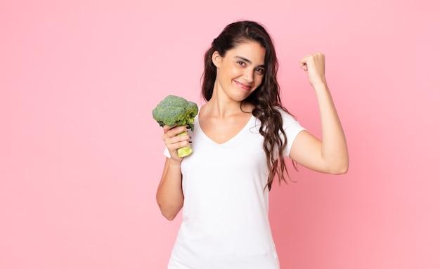 Bela jovem segurando um brócolis