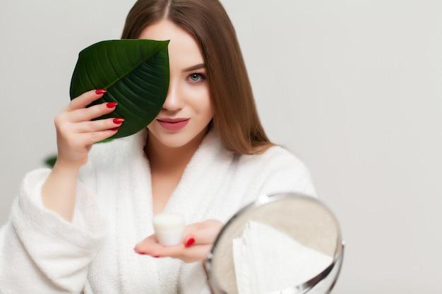 Bela jovem segurando um creme para cuidar do rosto no banheiro