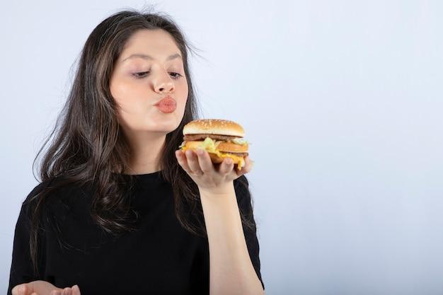 Bela jovem segurando um delicioso hambúrguer de carne e com vontade de comer.