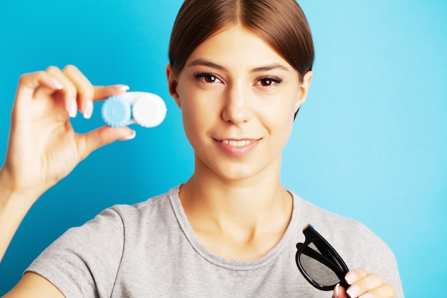 Bela jovem segurando um recipiente com lentes de contato para a visão