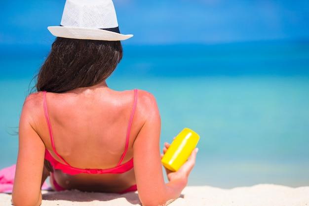 Bela jovem segurando um suncream deitado na praia tropical