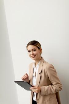 Bela jovem segurando um tablet digital em um escritório moderno
