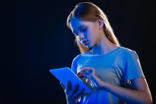 Bela jovem segurando um tablet enquanto lê um livro