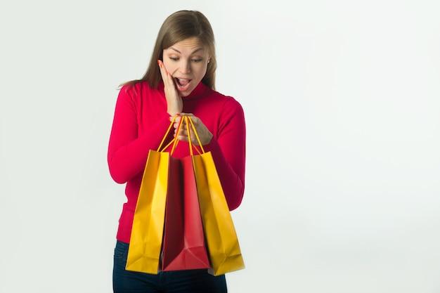 Bela jovem segurando uma compra em sacos macios em uma parede branca
