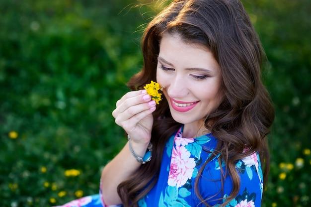 Bela jovem segurando uma flor no parque de verão