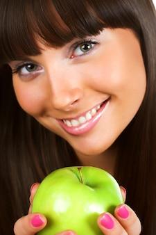 Bela jovem segurando uma maçã verde