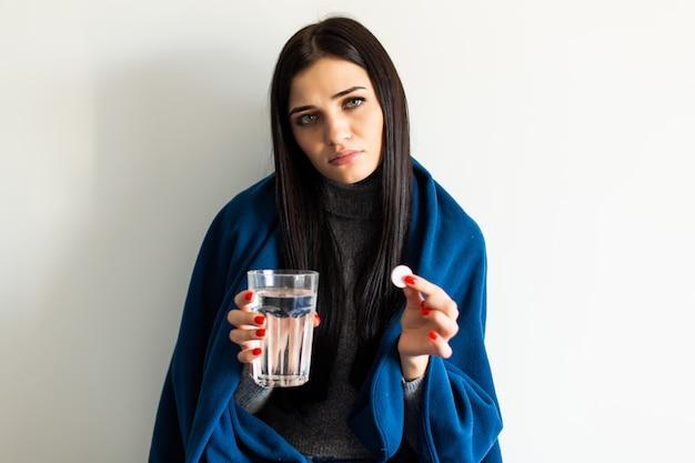 Bela jovem segurando uma manhã depois da pílula e um copo de água em casa