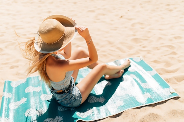 Bela jovem sentada na areia na praia