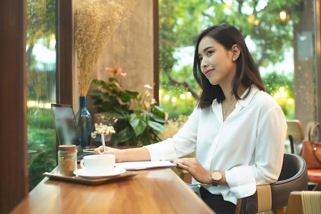 Bela jovem sentada na cadeira está pensando em trabalhar usando o laptop com uma expressão confiante no rosto inteligente, pensando sério, tecnologia de educação e conceito de pessoas.
