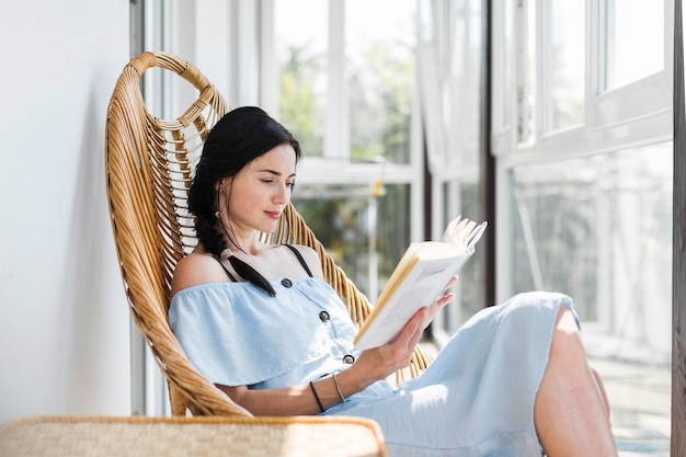 Bela jovem sentada na cadeira lendo livro