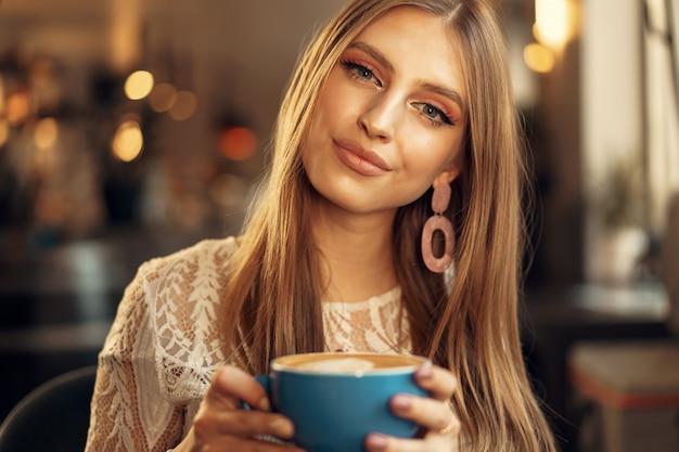 Bela jovem sentada na cafeteria, desfrutando de sua bebida