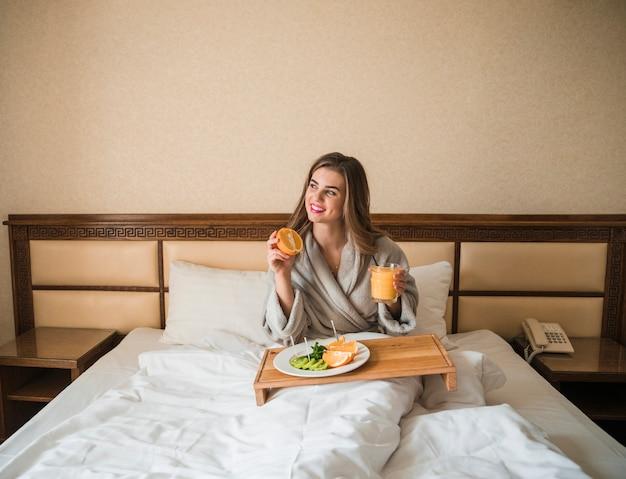Bela jovem sentada na cama com frutas e suco no café da manhã